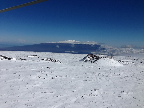 Photo courtesy of search-and-rescue pilot David Okita shows snow-covered Mauna Loa and the cindercone Pohaku o Hanalei in foreground, near where Sverdlov was spotted. Snow-covered Mauna Kea is seen in the distance.