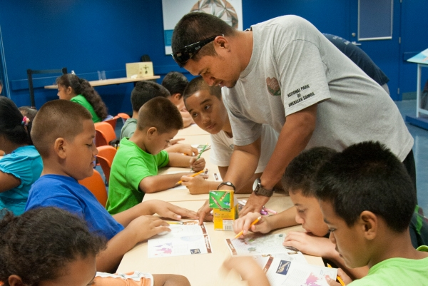 Quijano Taotua from Manulele Elementary School assists youth complete their activity books to become National Park of American Samoa Junior Rangers.