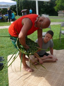Bolly Helekahi helps a visitor make a coconut leaf hat.