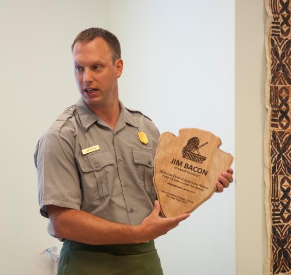 Superintendent Jim Bacon holding an arrowhead plaque.